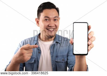 Portrait Of Young Young Asian Man Presenting Smart Phone Mockup With Happy Cheerful Expression, Poin