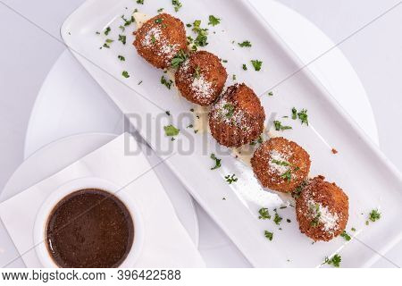 Overhead View Of Parmesan Topped Risotto Arancinis Italian Meatballs Lined Up On A Rectangular Plate
