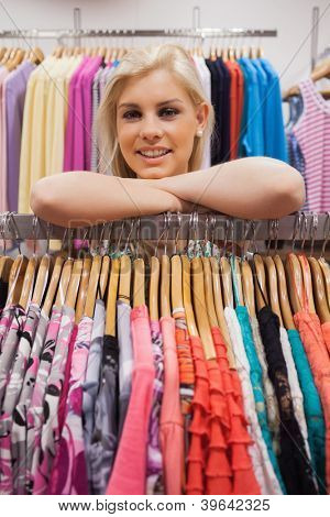 Woman lean on a clothes rack of a boutique looking satisfied