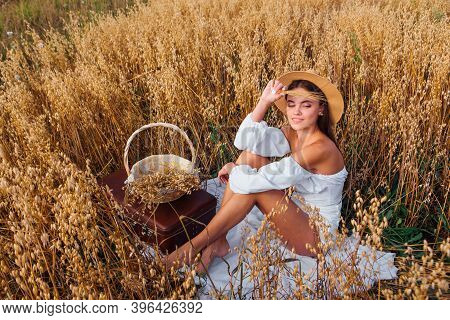 Young Beautiful Woman With Straw Hat Sitting At Golden Oat Field Near The Basket With Ears Of Oats.