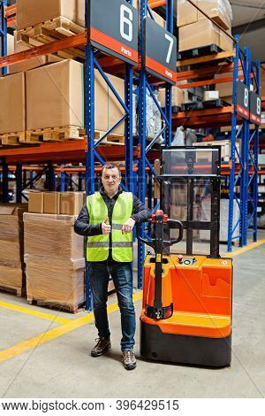 Storehouse Employee In Uniform Working On Forklift In Modern Automatic Warehouse. Worker Showing Thu
