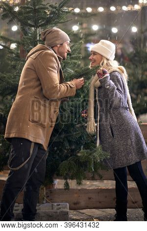 A young lovely couple in romantic moments around christmas tree in a magical night of a snowy weather in the city. Christmas tree, love, relationship, Xmas, snow