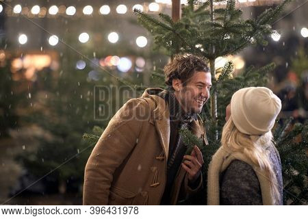 A young cheerful couple having fun with the christmas tree in the magical night on a snowy weather in the city. Christmas tree, love, relationship, Xmas, snow