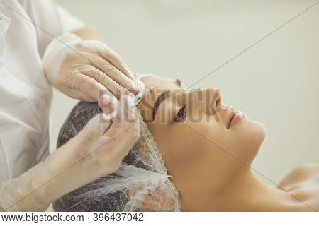 Woman Recieving Injection Of Anti-aging Botox Filler To Forehead Skin From Professional Cosmetologis