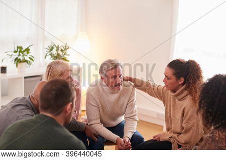 Group Consoling Man Speaking At Support Group Meeting For Mental Health Or Dependency Issues