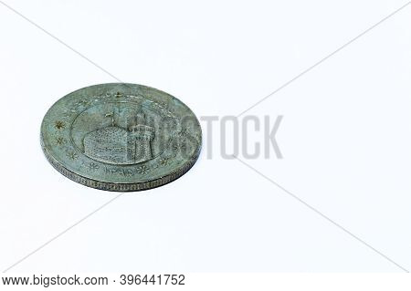 An Old Coin Of Persian Origin On A White Background