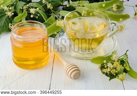 Jar Of Linden Honey, Cup Of Linden Tea And Branch With Linden Flowers On Wooden Table.