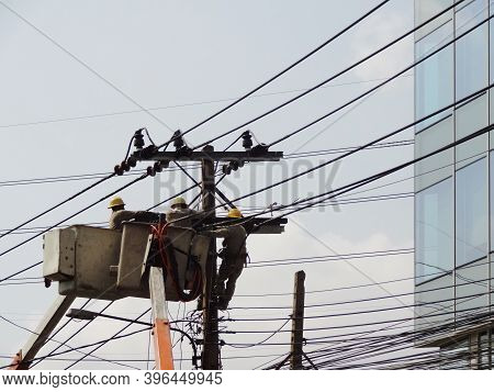 3 Electricians Fixing Repair Maintenance High Voltage Electric Power Pole On  Boom Lift Next To Glas