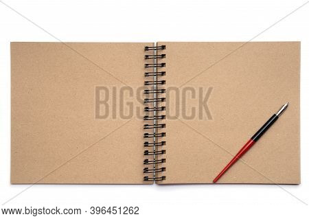 Photo Of An Empty, Unfolded Notebook On A Spiral, With Sheets Of Kraft Paper And A Pen On A White Is