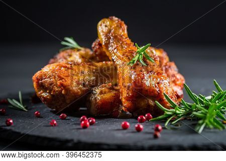 Hot spicy chicken legs with herbs on black background