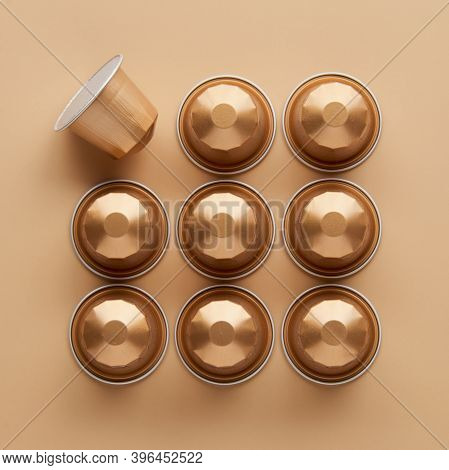 Caffeine, Hot Drinks And Objects Concept - Close Up Of Golden Capsules Or Pods For Coffee Mashine On