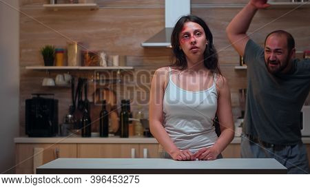 Alcoholic Man Abusing His Wife Sitting In The Kitchen. Traumatised Abused Terrified Beaten Wife Cove