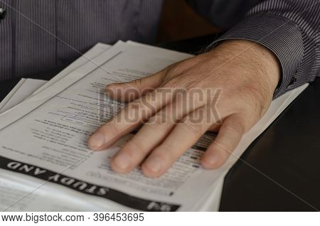 Emigration Or Distance Learning Concept. Language Exam. The Hand Of An Adult Man Lies On Top Of The