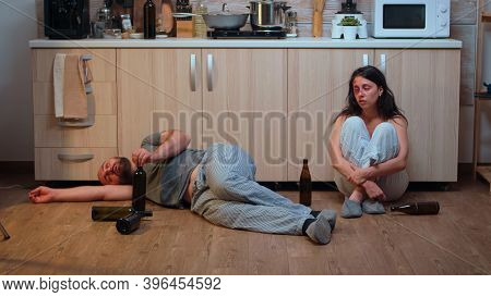 Alcoholic Man Lying On The Floor Near Beaten Wife Surrounded By Empty Bottles. Drunk Aggressive Husb
