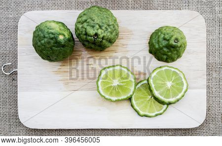 Bergamot Fruit Cutting Slices On Wooden Clipping Board On Sackcloth Background. Bergamot Material Of