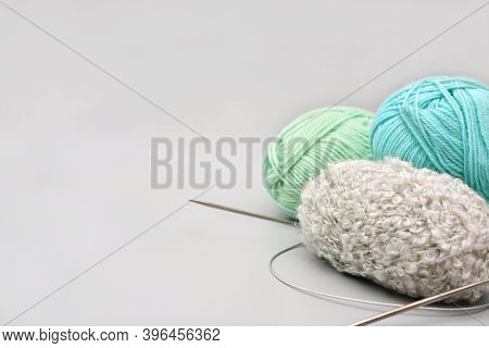 Variety Of Knitting Yarn And Needles On Grey Background. Needlecraft And Winter Hobby. Needlework An
