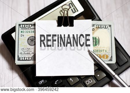 White Paper With Text Refinance With Dollars On Calculator With Pen