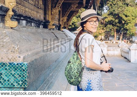 Portrait Of Asian Tourist Visiting Wat Xieng Thong An Iconic Temple In Luang Prabang, The Unesco Wor