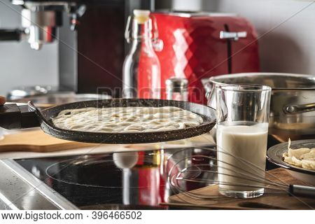 Pancake Is Cooking In A Hot Frying Pan. Concept Of The Process Of Making Homemade Pancakes In Your O