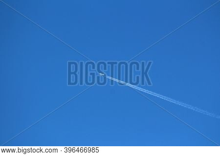 High Speed White Passenger Plane Flying At High Altitude Over Clear Blue Sky Leaving Two White Contr