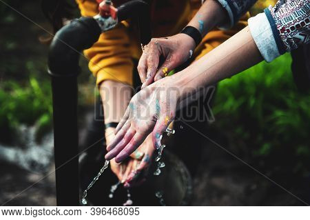 Shallow Depth Of Field (selective Focus) Image With Young Women Washing Their Hands From Painting Co