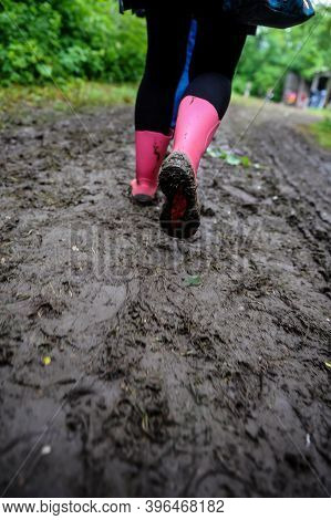 Shallow Depth Of Field (selective Focus) Image With A Young Lady Wearing Pink Rubber Boots On A Mudd