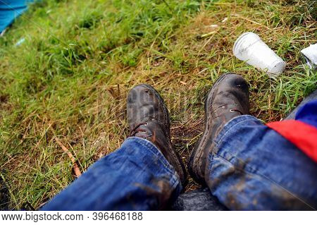 Details With The Muddy Boots And Jeans Of A Man Sitting In A Tent At A Music Festival During A Rainy