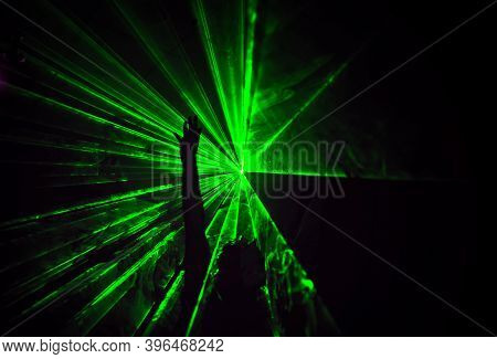 Trippy Night Image With People Dancing Outdoors In A Forest Music Festival With Laser Beams In The B