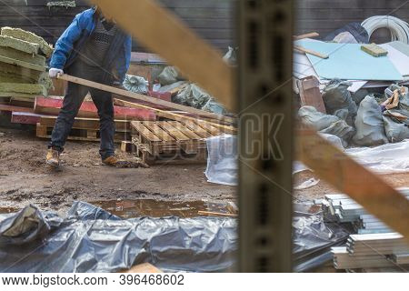 View From House Through Window On The Worker In Protective Gloves Who Is Working On The Construction