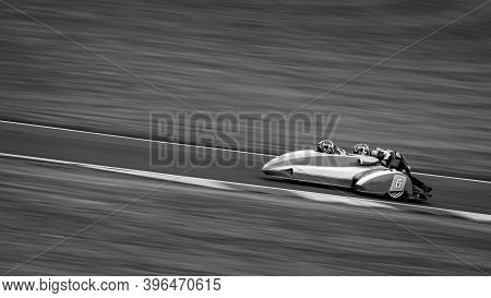 A Monochrome Panning Shot Of A Racing Sidecar As It Corners On A Track.