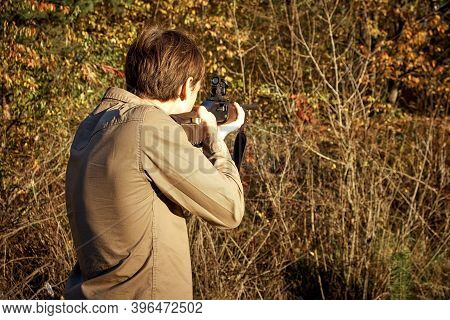 Hunter Hunting In The Forest With A Hunting Rifle. A Man With A Gun.