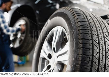 Close Up View Of Car Wheel Near Technician Maintaining Car On Blurred