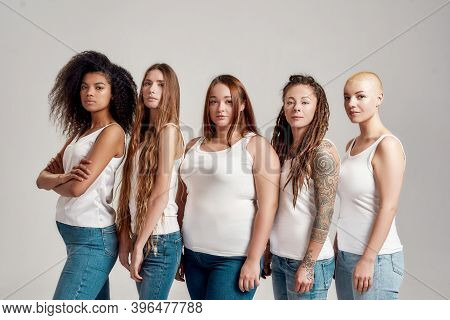 Group Of Five Beautiful Diverse Young Women In White Shirt And Jeans Looking At Camera While Posing