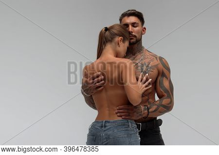 Muscular Tattooed Man Embracing Slim Topless Woman In Panties On Gray Background