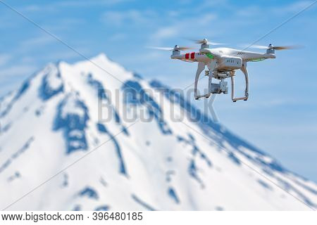Innovative Quadcopter Drone Uav With Camera Flying In Blue Sky On Background Mountain, Rocky Volcani