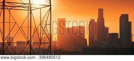 Downtown Los Angeles industrial skyline at sunset, power line in foreground.