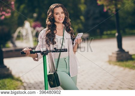 Photo Of Charming Cheerful Sporty Girl Drive Segway Hold Telephone Wear Striped Shirt Green Jeans Ba