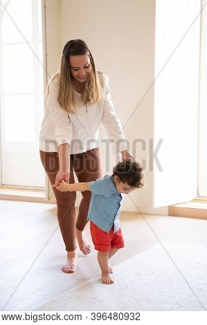 Happy Caucasian Mother Holding Son Hands And Helping Him To Walk. Cute Curly Mixed-race Little Boy L
