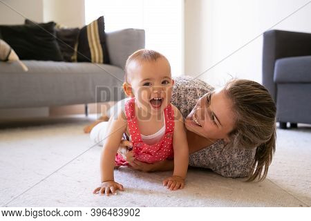 Joyful Mom And Little Girl Lying On Carpet In Living Room. Happy Blonde Mom Playing With Cheerful Da