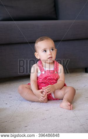 Lovely Little Baby Sitting On Carpet Barefoot In Living Room. Cute Thoughtful Girl In Red Dungarees