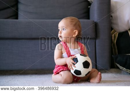 Adorable Baby Girl Holding Soccer Ball, Sitting On Carpet Barefoot And Looking Away. Cute Infant In