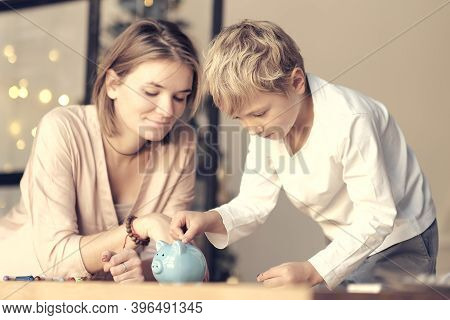 Mother And Child Putting Coin Into Piggy Bank. Education Of Children In Financial Literacy. Money, C