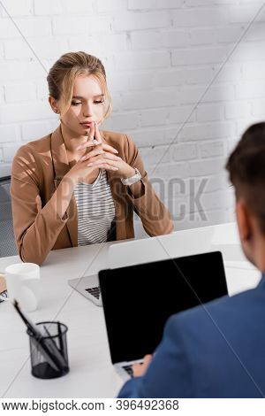Female Executive Looking At Laptop, While Sitting At Workplace With Blurred Co-worker On Foreground