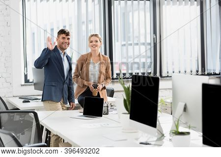 Businessman With Waving Hand, Looking At Camera, While Standing Near Co-worker During Break In Offic
