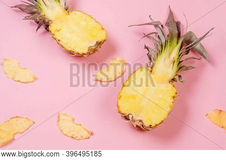 Ripe Juicy Pineapple On Pink Background And Dried Pineapple Wedges Around. Fruit Chips. Healthy Eati