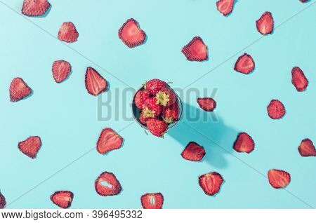 Ripe Raw Strawberry And Dried Strawberry Slices Chips Scattered On Blue Background. Fruit Chips. Hea