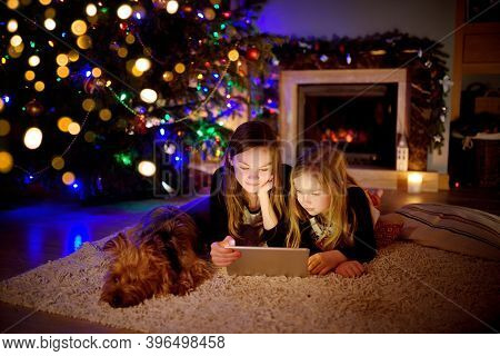 Two Cute Young Sisters Using A Tablet Pc At Home By A Fireplace In Warm And Cozy Living Room On Chri
