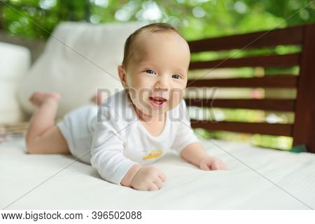Cute Three Months Old Baby Boy Lying On His Tummy. Baby During Tummy Time. Cute Child Learning To Cr