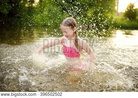 Cute Little Girl Wearing Swimsuit Playing By A River On Hot Summer Day. Adorable Child Having Fun Ou