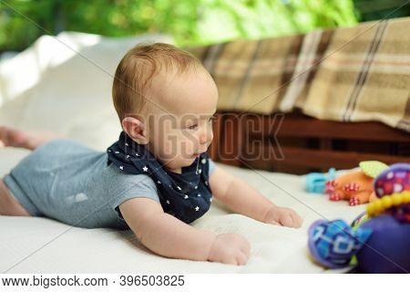 Cute Three Months Old Baby Boy Playing With His Colourful Toys Outdoor. Baby During Tummy Time. Cute